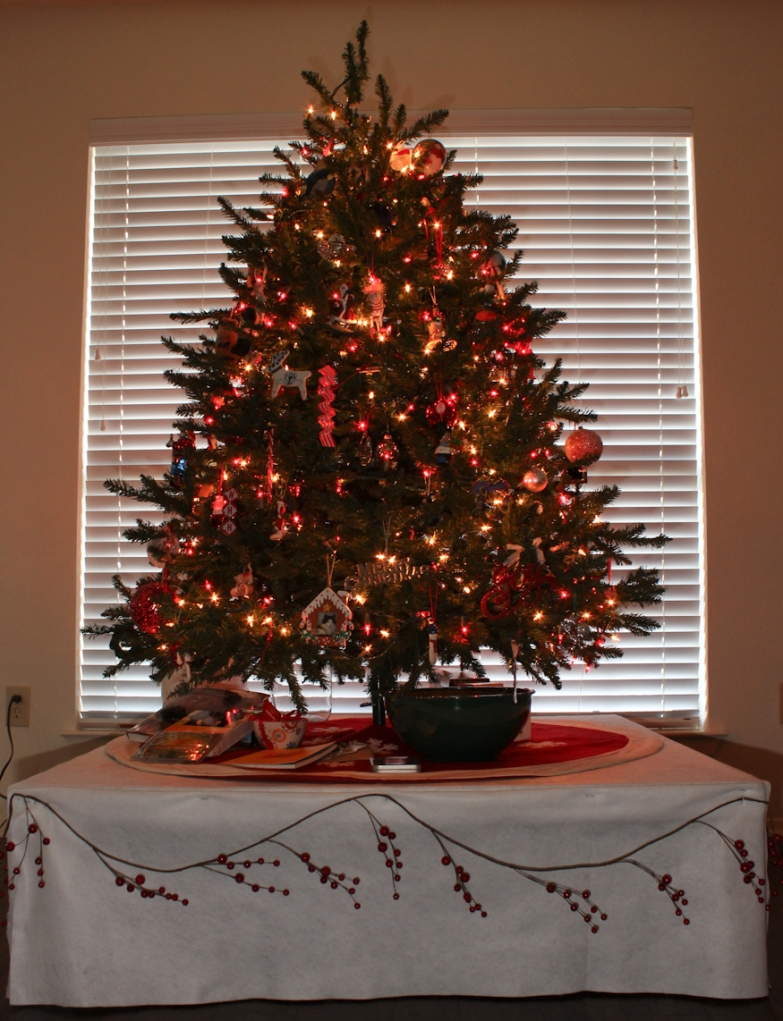 Overall view of the tree, tree stand, and white felt and garland used to decorate the stand.