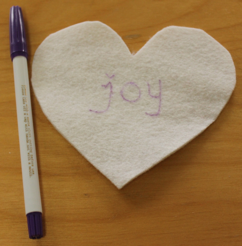Drawing the word before embroidering.