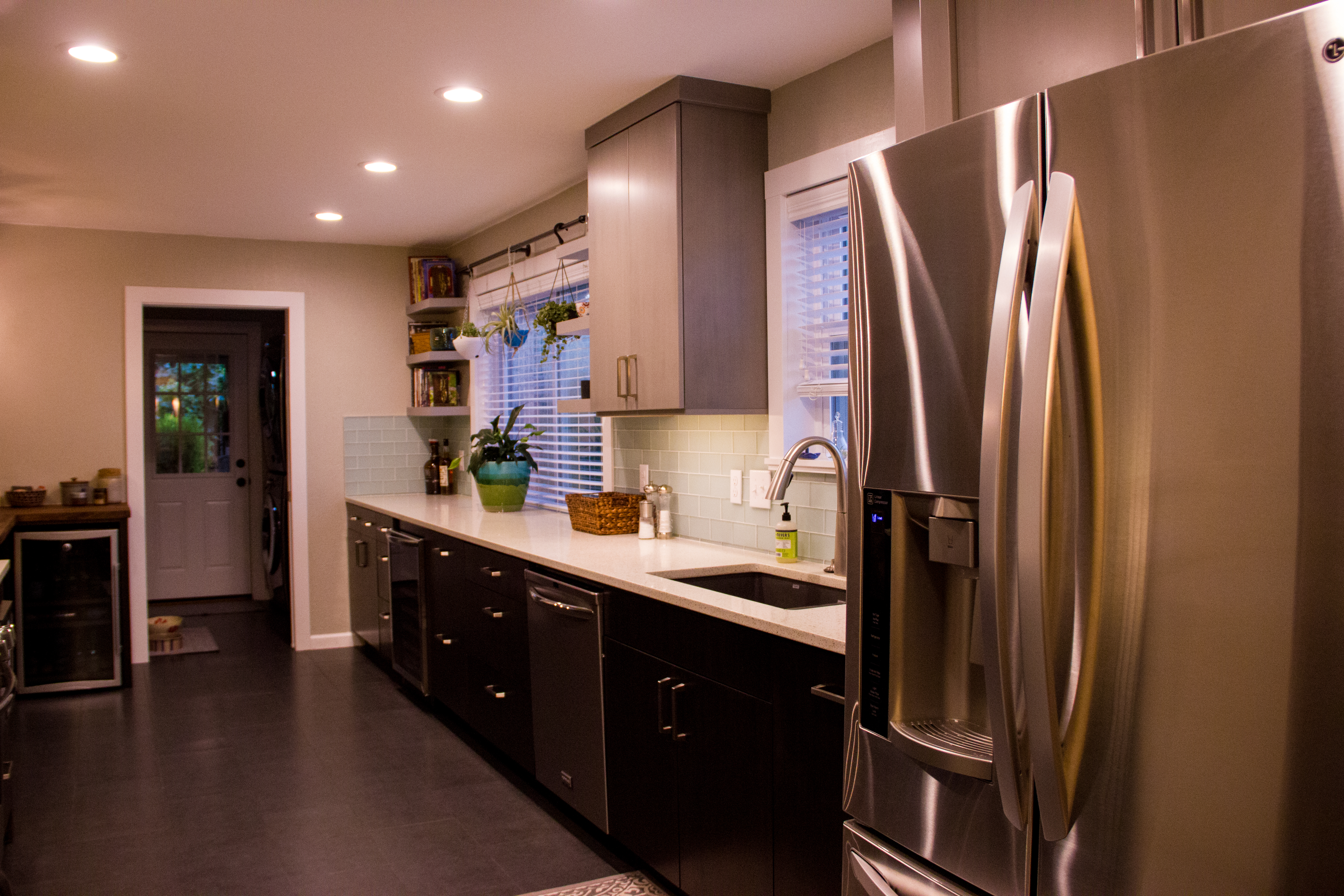the cabinets above the fridge and the panel on its left side make the fridge look built in and the cabinets have special vertical dividers for baking pan